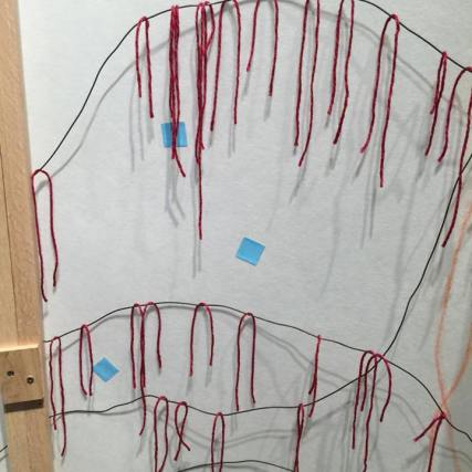 viewers were invited to add ancestor and family prayers by draping red string on the rippling black wires